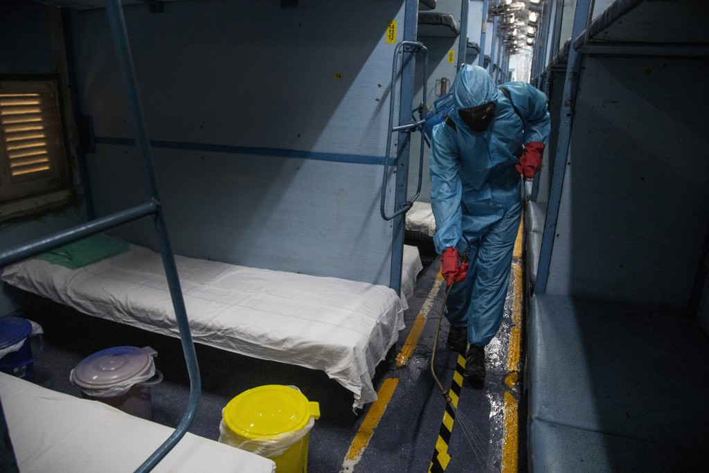 A health worker in personal protective equipment sanitizes a compartment of a train prepared as COVID-19 care centre in the wake of spike in the numbe...
