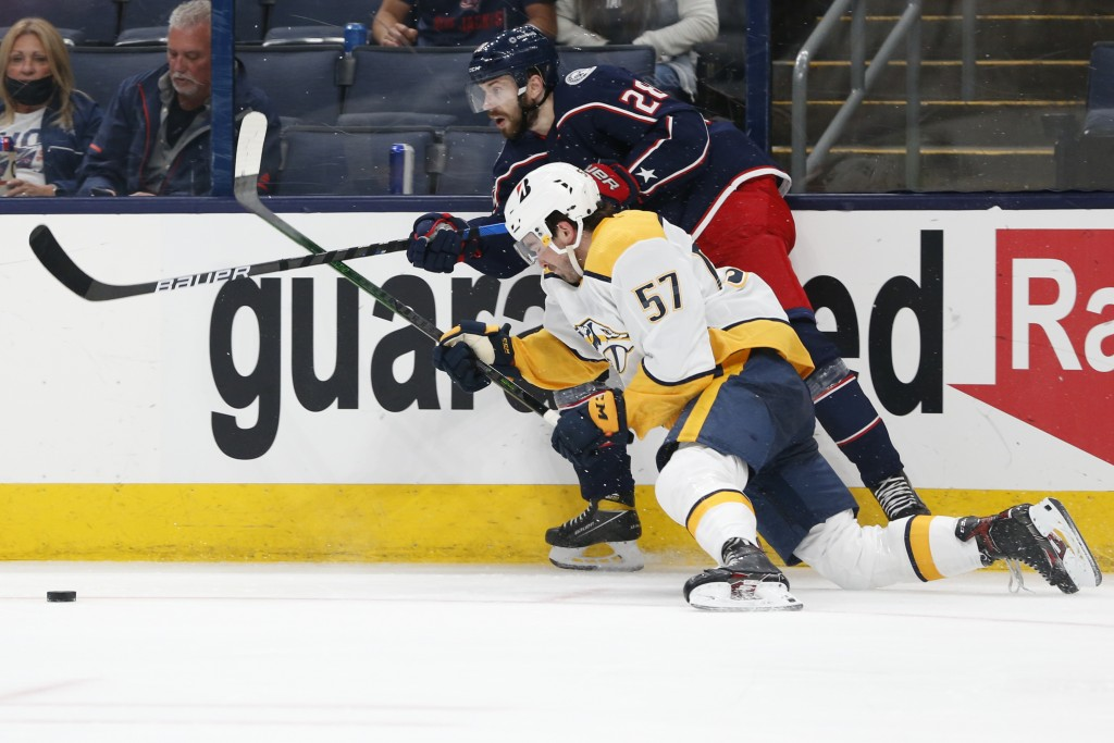 Columbus Blue Jackets' Oliver Bjorkstrand, top, passes the puck as Nashville Predators' Dante Fabbro defends during the second period of an NHL hockey...