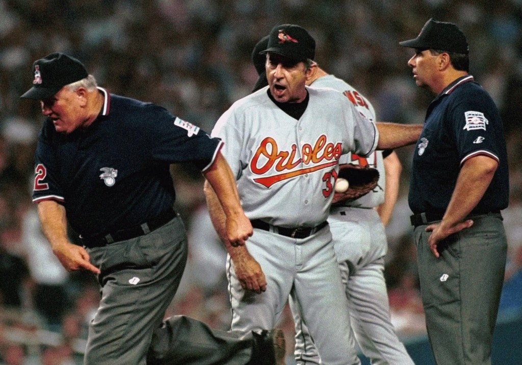 FILE - In this Friday, July 2, 1999 file photo, Baltimore Orioles manager Ray Miller, center, is ejected from the game by first base umpire Larry Barn...