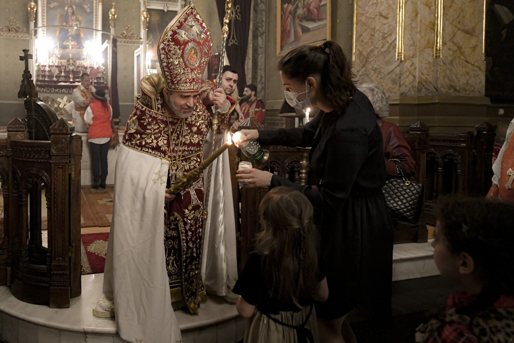 Members of the Armenian community in Romania, receive the holy light from Iraq-born Archbishop Datev Hagopian during the Easter religious service, at ...