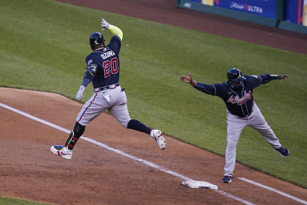 Atlanta Braves' Marcell Ozuna celebrates his grand slam with first base coach Eric Young Sr. during the third inning of the team's baseball game again...