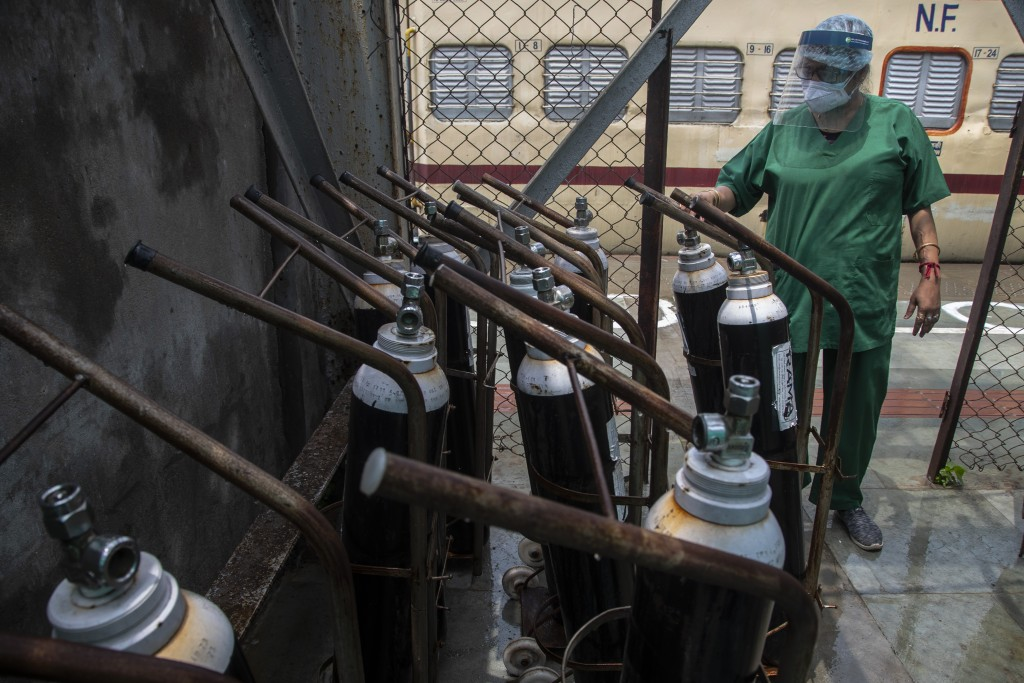 A health worker checks oxygen cylinders stored next to a train prepared as COVID-19 care centre in the wake of spike in the number of positive coronav...