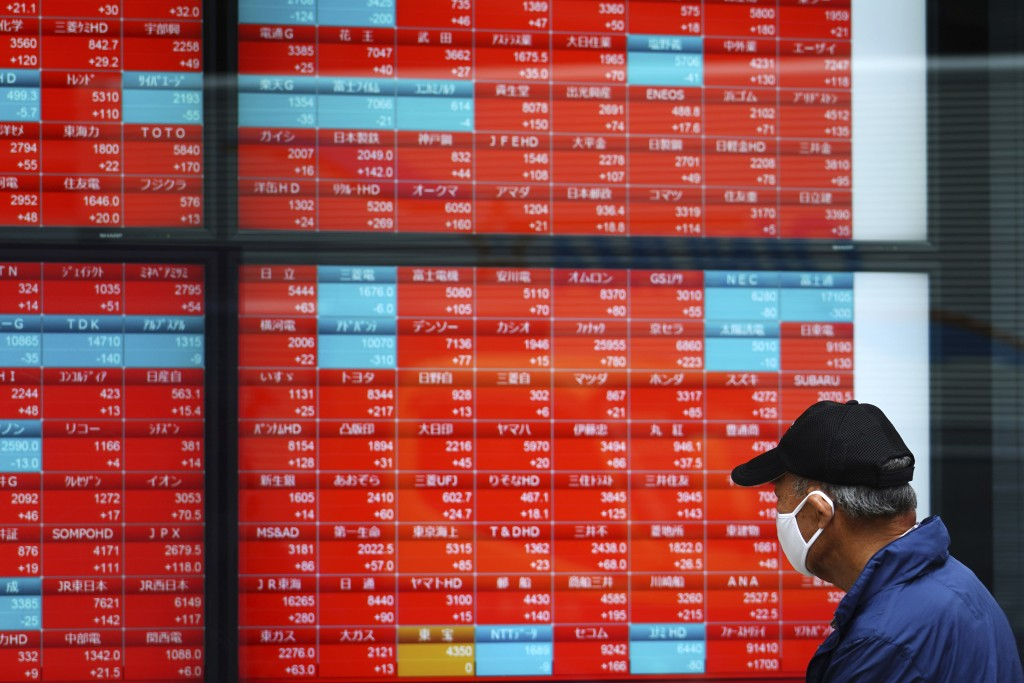 A man wearing a protective mask looks at an electronic stock board showing Japan's Nikkei 225 index at a securities firm Thursday, May 6, 2021, in Tok...