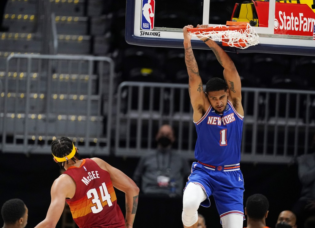 New York Knicks forward Obi Toppin, right, hangs from the rim after dunking the ball for a basket while Denver Nuggets center JaVale McGee defends in ...