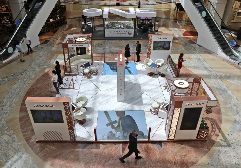 Sales people from two major real estate developers wait for customers at their shopping mall stands, in Dubai, United Arab Emirates, Wednesday, May 5,...