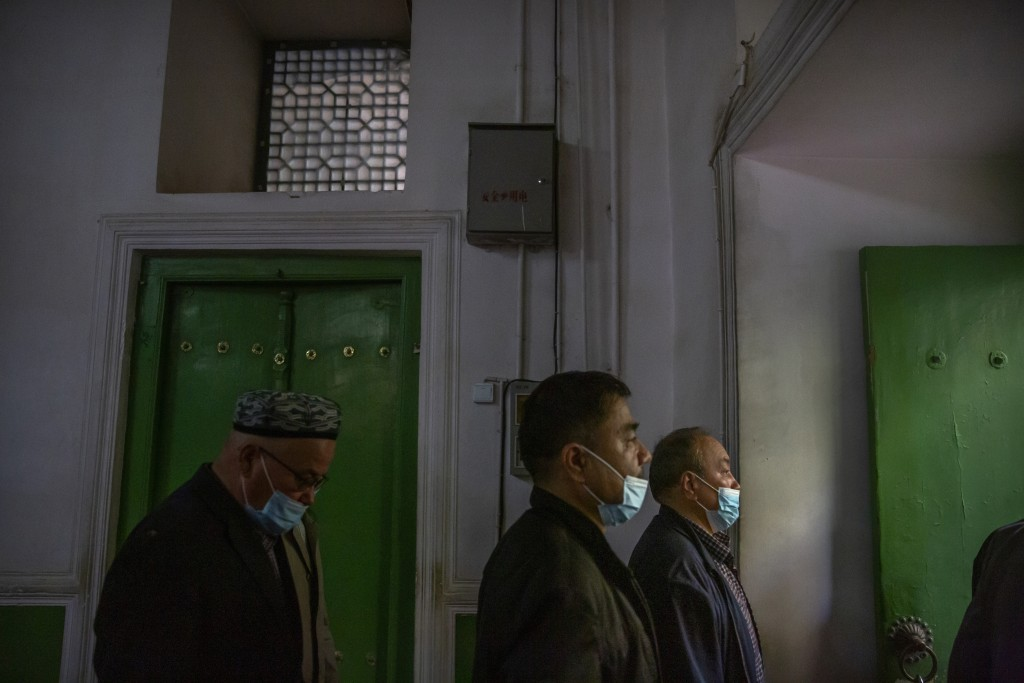 Uyghurs and other members of the faithful leave after prayer services at the Id Kah Mosque in Kashgar in western China's Xinjiang Uyghur Autonomous Re...