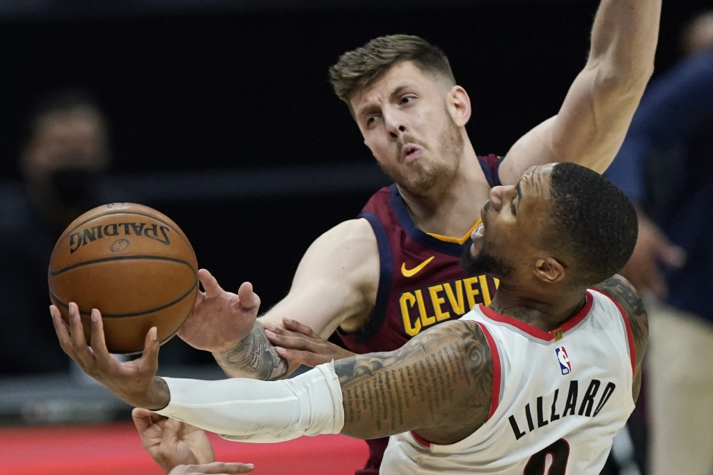 Portland Trail Blazers' Damian Lillard (0) drives to the basket against Cleveland Cavaliers' Isaiah Hartenstein during the second half of an NBA baske...