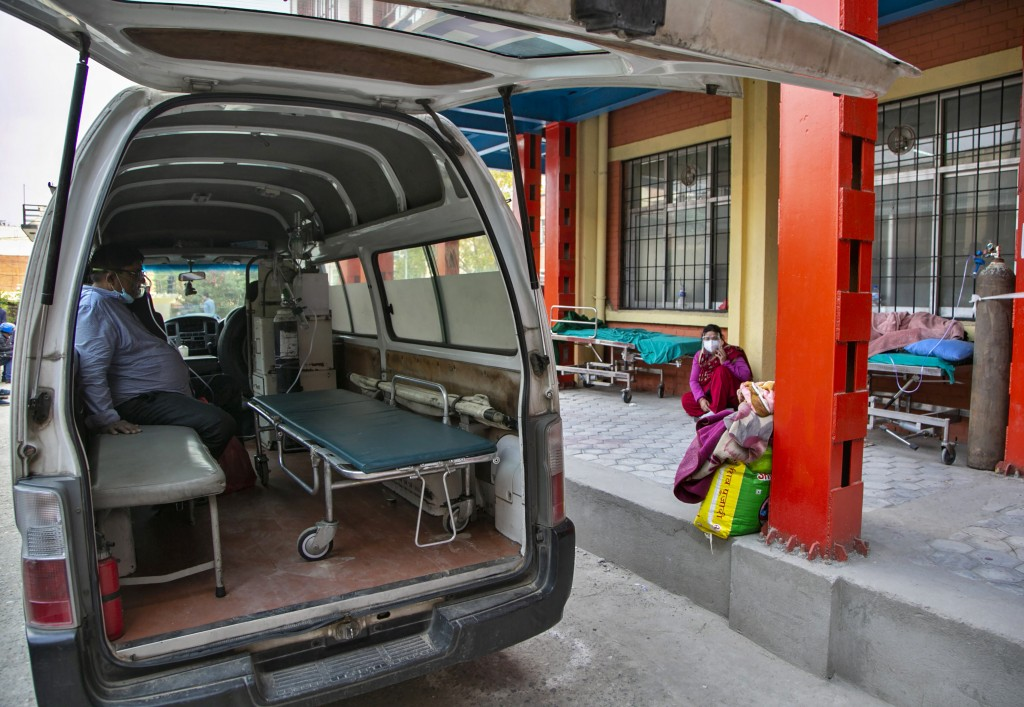 A COVID-19 patient receives oxygen in an ambulance outside an emergency ward as he waits for a bed to be allotted at a hospital in Kathmandu, Nepal, T...