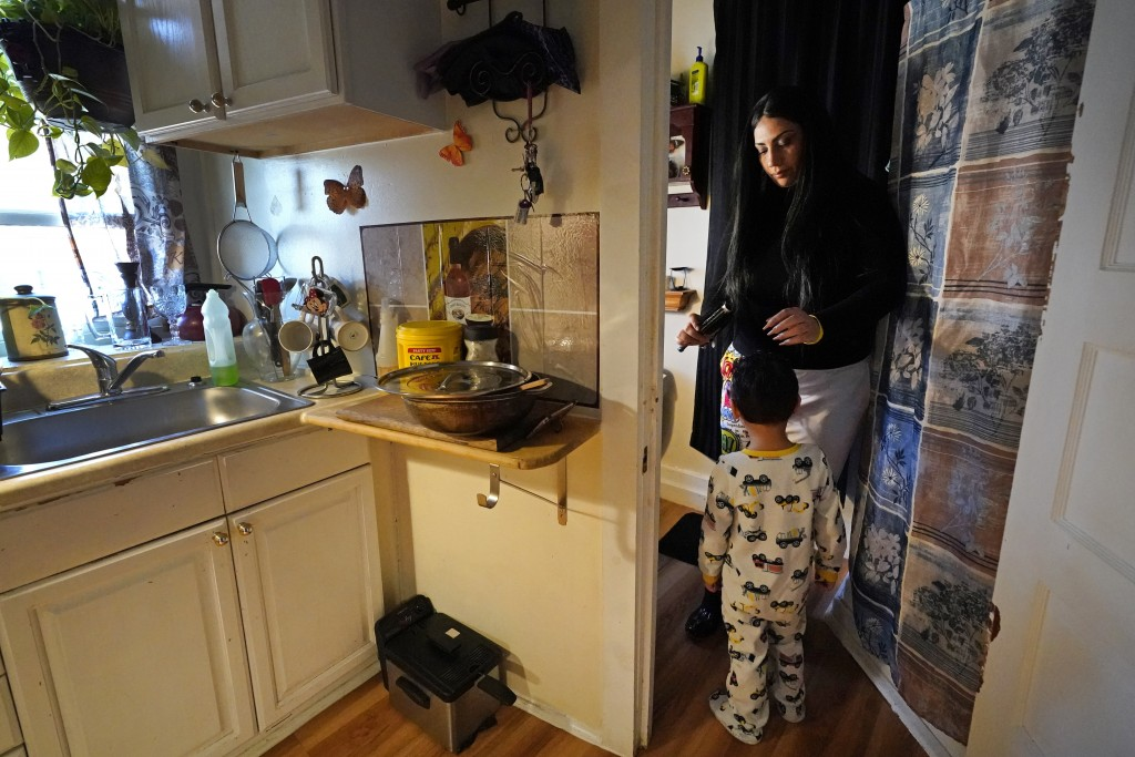 FILE - In this March 10, 2021, file photo, Isabel Miranda brushes the hair of her 4-year-old son, Julian, in their rental apartment in Haverhill, Mass...