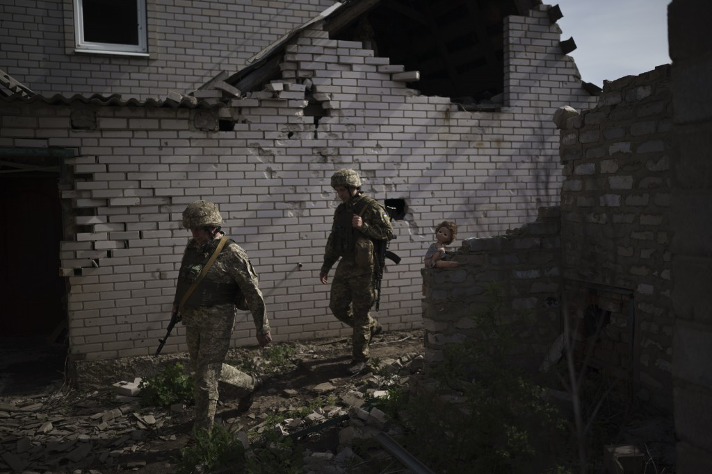 FILE - In this Tuesday, May 4, 2021 file photo, Ukrainian soldiers walk next to a destroyed house near a fighting position on the line of separation f...