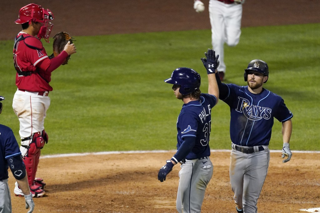Tampa Bay Rays' Brandon Lowe, right, is congratulated by Brett Phillips, center, after hitting a three-run home run as Los Angeles Angels catcher Kurt...
