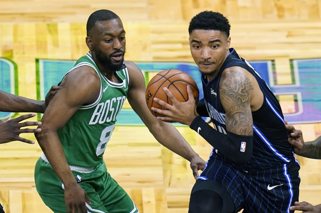 Orlando Magic guard Gary Harris, right, makes a move to get past Boston Celtics guard Kemba Walker (8) during the first half of an NBA basketball game...