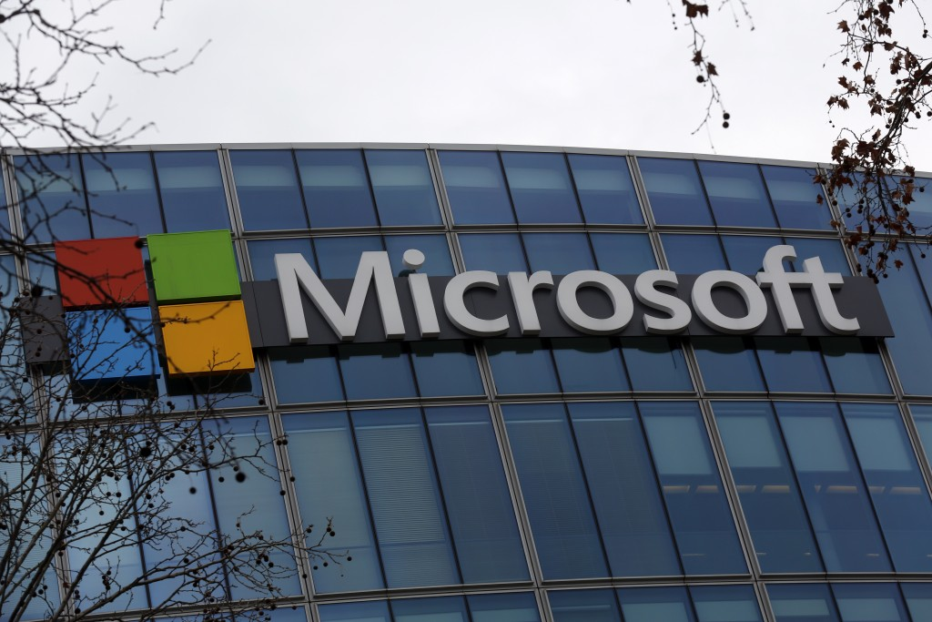 FILE - This Jan. 8, 2021 file photo shows the logo of Microsoft displayed outside the headquarters in Paris. Microsoft's business beat Wall Street exp...