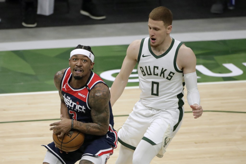 Washington Wizards' Bradley Beal, left, drives to the basket against Milwaukee Bucks' Donte DiVincenzo during the first half of an NBA basketball game...