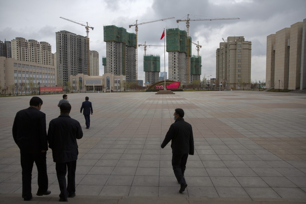 Chinese government officials walk across a plaza near a display with the Chinese flag at the Xinjiang Islamic Institute, as seen during a government o...