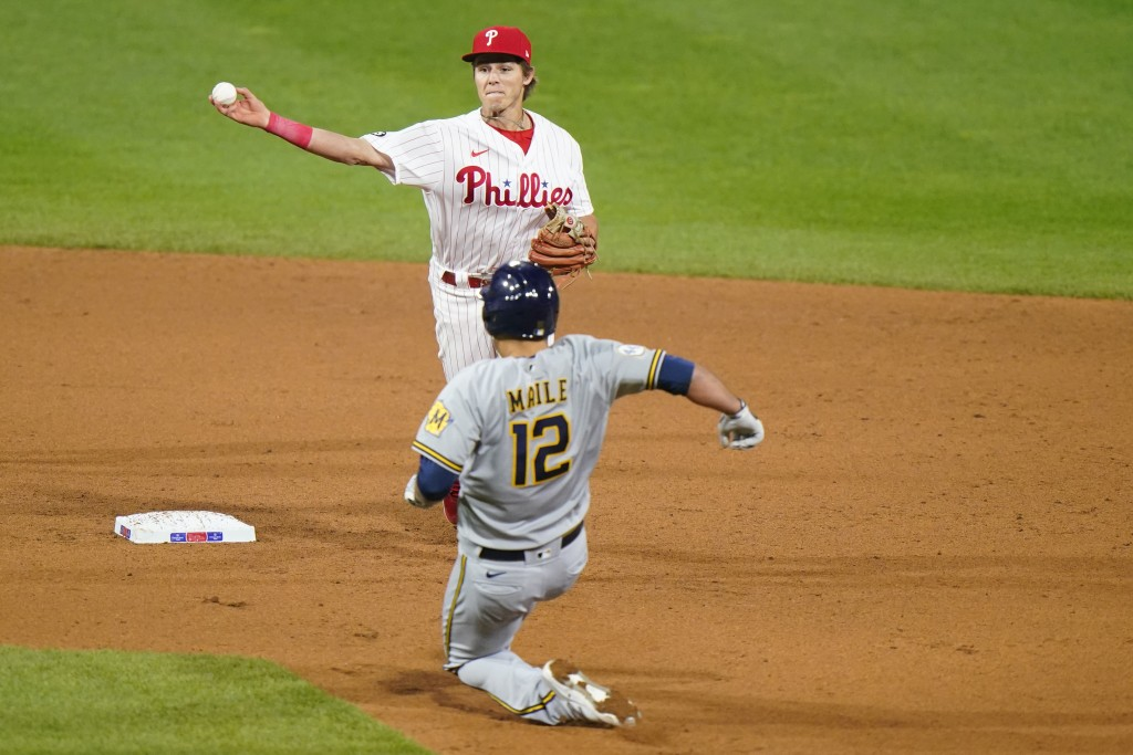 Philadelphia Phillies second baseman Nick Maton, top, throws to first after forcing out Milwaukee Brewers' Luke Maile at second on a double play hit b...
