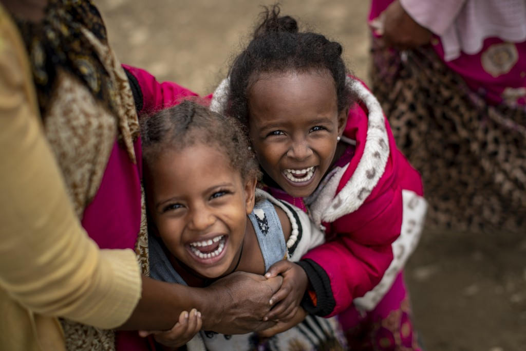 Two displaced Tigrayan girls giggle next to their mother, left, as their photograph is taken outside the Hadnet General Secondary School which has bec...
