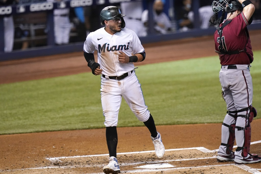 Miami Marlins' Miguel Rojas, left scores past Arizona Diamondbacks catcher Stephen Vogt (21) on a single hit by Brian Anderson during the first inning...