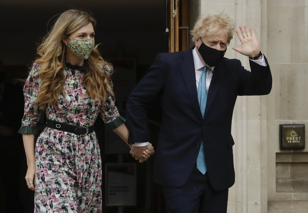 British Prime Minister Boris Johnson waves as he leaves a polling station with his partner Carrie Symonds after casting his vote in local council elec...