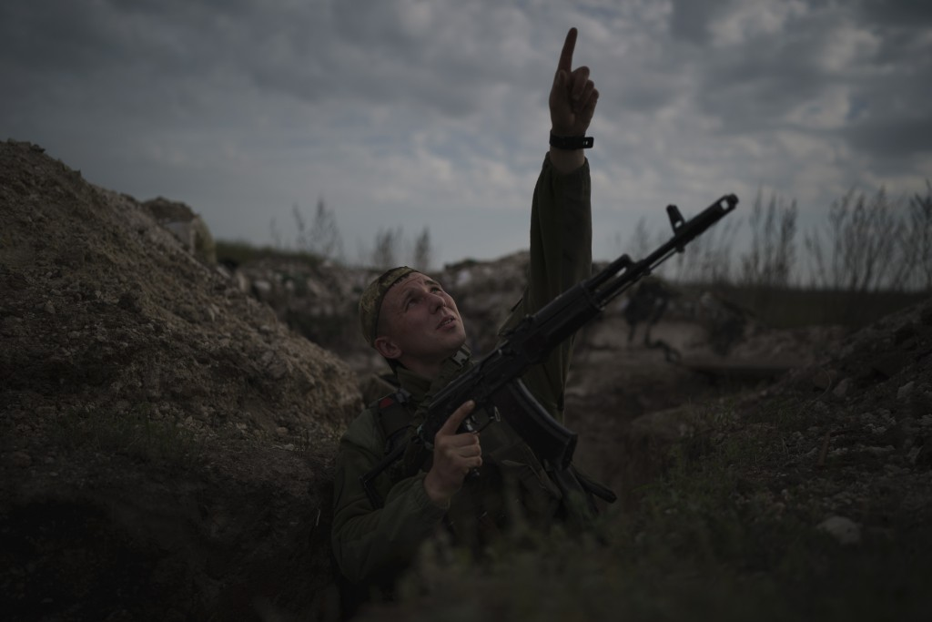 FILE - In this Monday, May 3, 2021 file photo, a Ukrainian soldier points at a passing helicopter as he stands in a trench on the line of separation f...