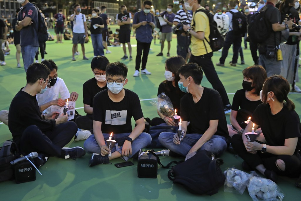 In this June 4, 2020 photo, Hong Kong democracy activist Joshua Wong, second left, holds candle as he joins others for a vigil to remember the victims...