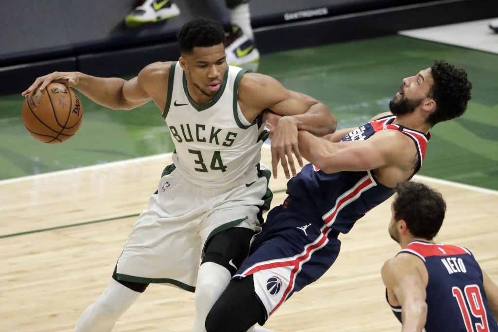 Milwaukee Bucks' Giannis Antetokounmpo (34) commits a charging foul against Washington Wizards' Anthony Gill during the first half of an NBA basketbal...