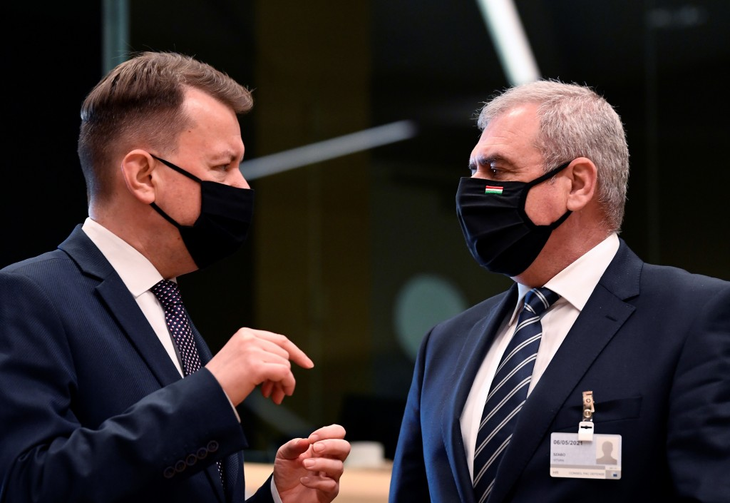 Poland's Defense Minister Mariusz Blaszczak, left, speaks with Hungary's Defense Minister Tibor Benko during a meeting of EU defense ministers at the ...