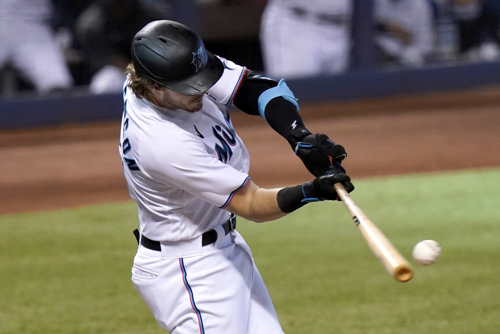 Miami Marlins' Brian Anderson hits an RBI-single to score Miguel Rojas during the first inning of a baseball game against the Arizona Diamondbacks, We...