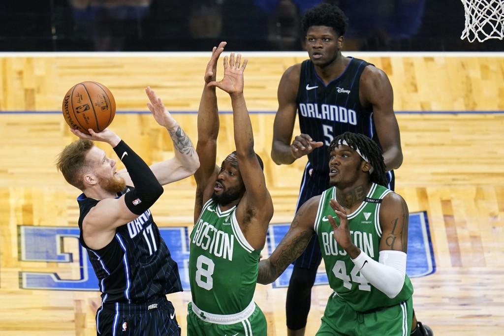 Orlando Magic forward Ignas Brazdeikis (17) takes a shot over Boston Celtics guard Kemba Walker (8) and center Robert Williams (44) as Magic center Mo...