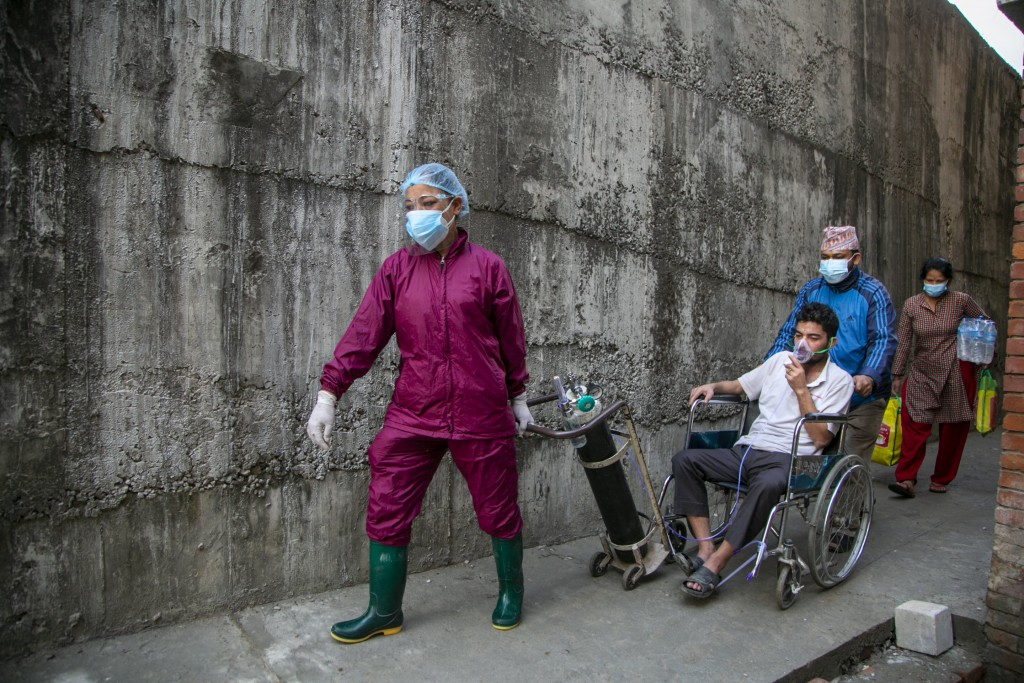A COVID-19 patient arrives at a hospital in Kathmandu, Nepal, Thursday, May 6, 2021. Nepal's main cities and towns including the capital Kathmandu has...