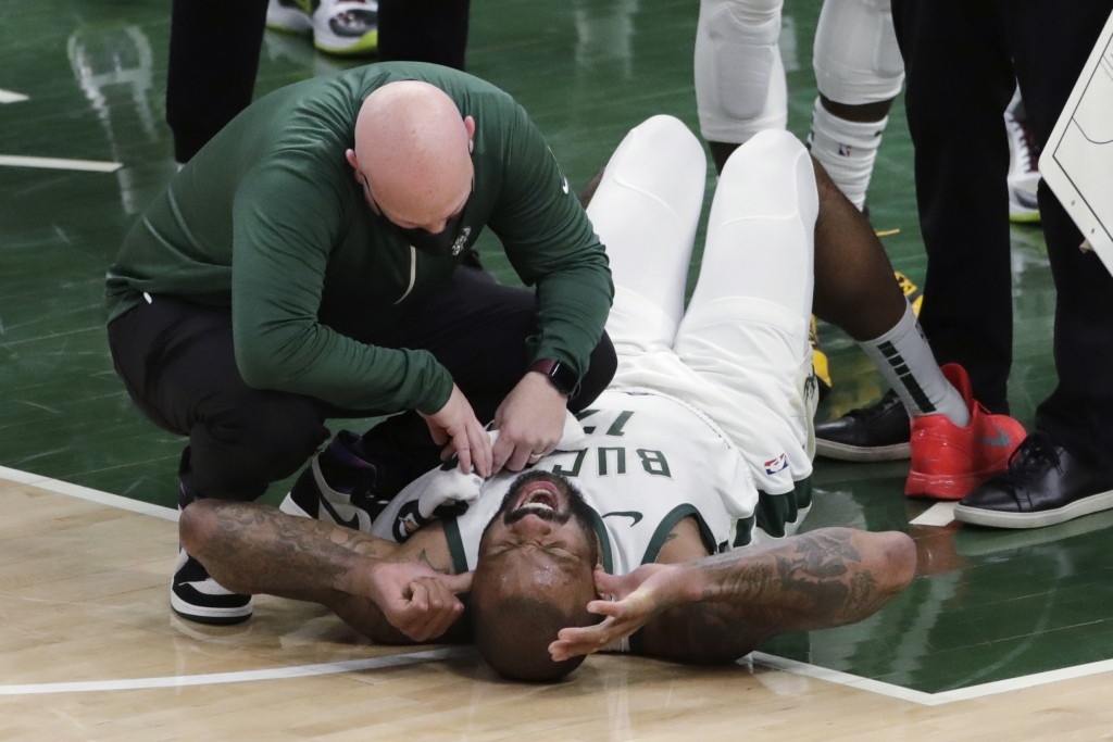 Milwaukee Bucks' P.J. Tucker is checked on by a trainer after suffering an injury during the second half of the team's NBA basketball game against the...