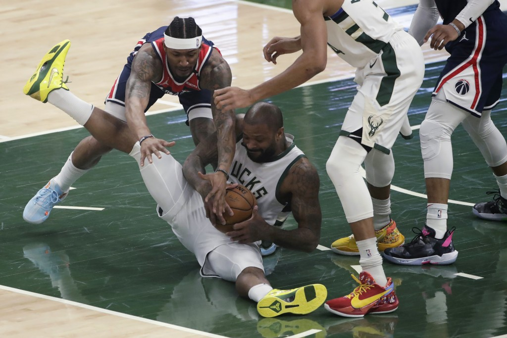 Milwaukee Bucks' P.J. Tucker and Washington Wizards' Bradley Beal compete for possession of the ball during the first half of an NBA basketball game W...