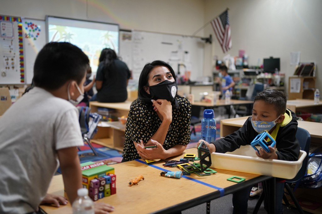 Teacher Juliana Urtubey, center, works with Brian Avilas, left, and Jesus Calderon Lopez, right, in a class at Kermit R Booker Sr Elementary School We...