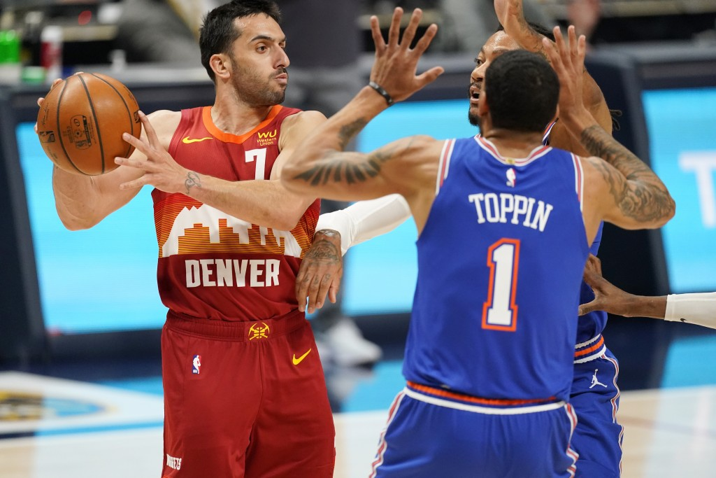 Denver Nuggets guard Facundo Campazzo, left, looks to pass the ball as New York Knicks forward Obi Toppin, front right, and guard Derrick Rose defend ...