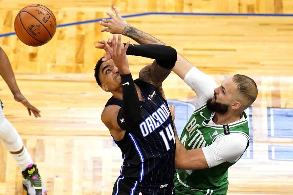 Boston Celtics guard Evan Fournier, right, knocks the ball from the hands of Orlando Magic guard Gary Harris (14) during the first half of an NBA bask...