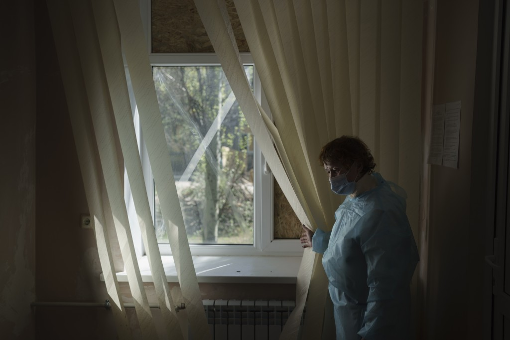 FILE - In this Wednesday, May 5, 2021 file photo, a doctor shows windows broken by shelling inside a hospital treating COVID-19 patients in the frontl...