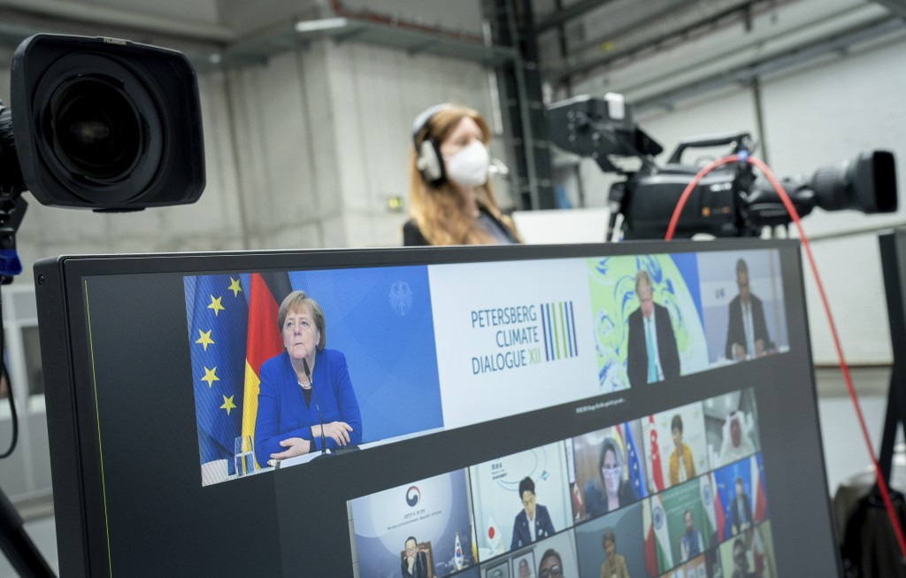 German Chancellor Angela Merkel (CDU) participates in the digital Petersberg Climate Dialogue, seen on the top left of a monitor, in Berlin, Germany, ...