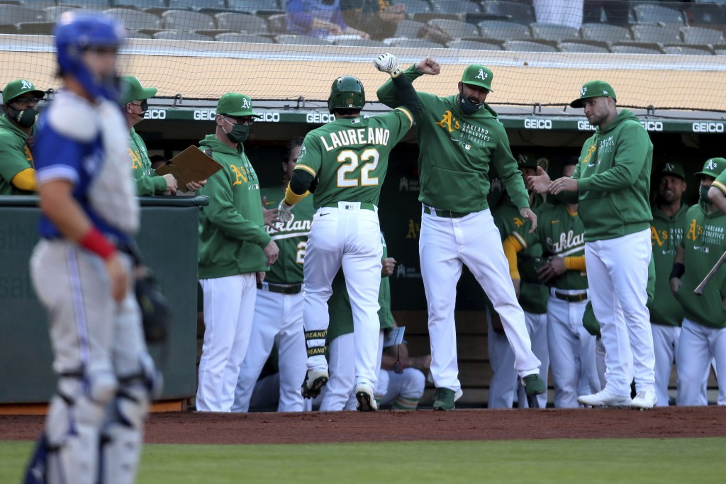 Oakland Athletics' Ramon Laureano (22) is congratulated by teammates after hitting a solo home run against the Toronto Blue Jays during the first inni...