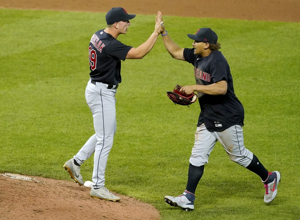 Cleveland Indians relief pitcher James Karinchak, left, and Josh Naylor celebrate after their baseball game against the Kansas City Royals Wednesday, ...
