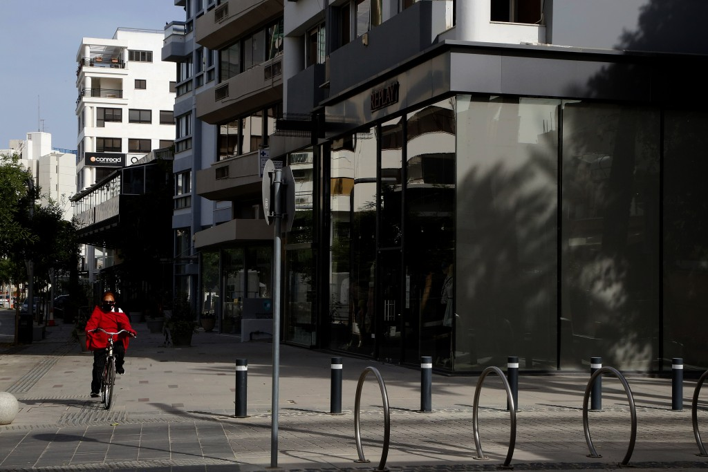 A woman wearing protective face mask drives her bicycle by closed shops amid COVID-19 pandemic restrictions government in central capital Nicosia, Cyp...