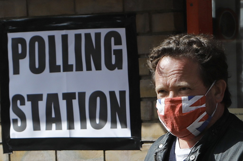 A man wearing a face covering leaves the polling station at St Albans Church after he voted, in London, Thursday, May 6, 2021. Millions of people acro...