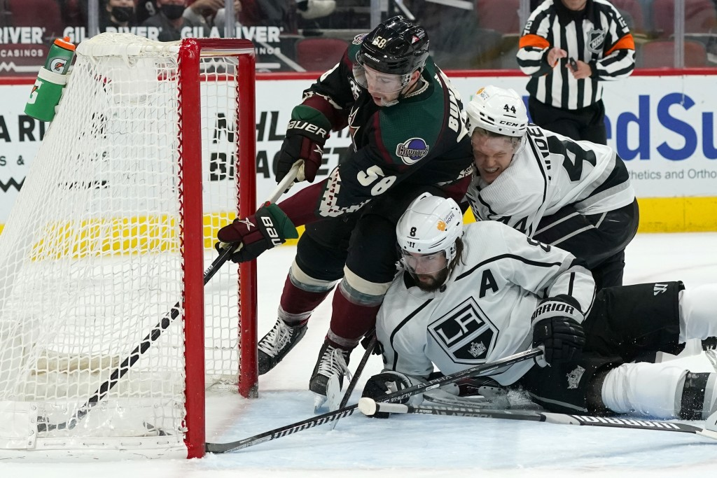 Arizona Coyotes left wing Michael Bunting (58) pushes the puck further into the net on a goal by Jakob Chychrun as Los Angeles Kings defensemen Drew D...