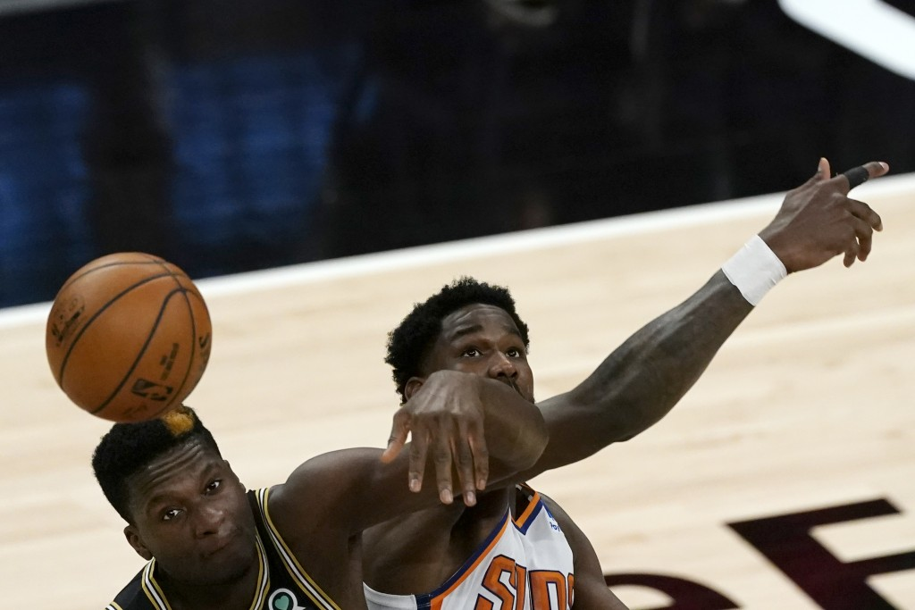 Atlanta Hawks center Clint Capela (15) and Phoenix Suns center Deandre Ayton (22) battle for the opening tip in the first half of an NBA basketball ga...