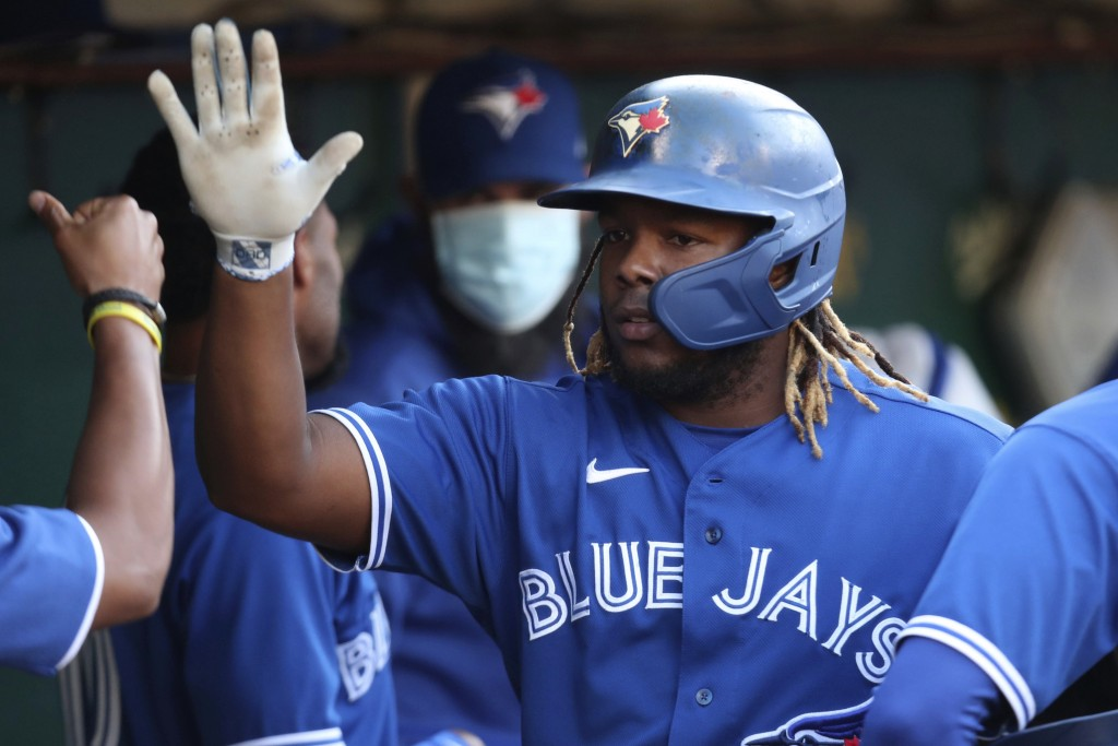 Toronto Blue Jays' Vladimir Guerrero Jr. is congratulated by teammates after scoring on a single by Randal Grichuk against the Oakland Athletics durin...