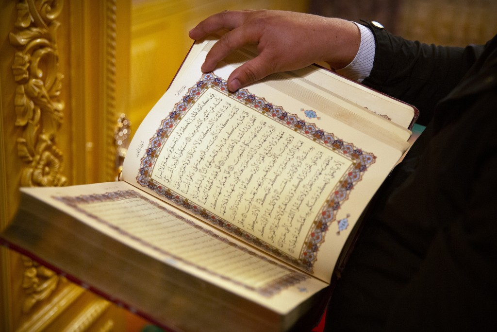 Tursunjan Mamat holds a copy of the Quran in the Arabic and Uyghur languages during a government organized visit for foreign journalists to his home i...