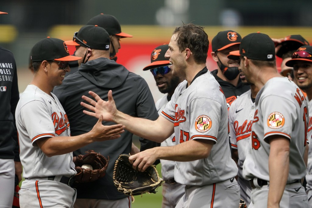 Baltimore Orioles starting pitcher John Means, center, greets shortstop Ramon Urias, left, after Means threw a no-hitter baseball game against the Sea...