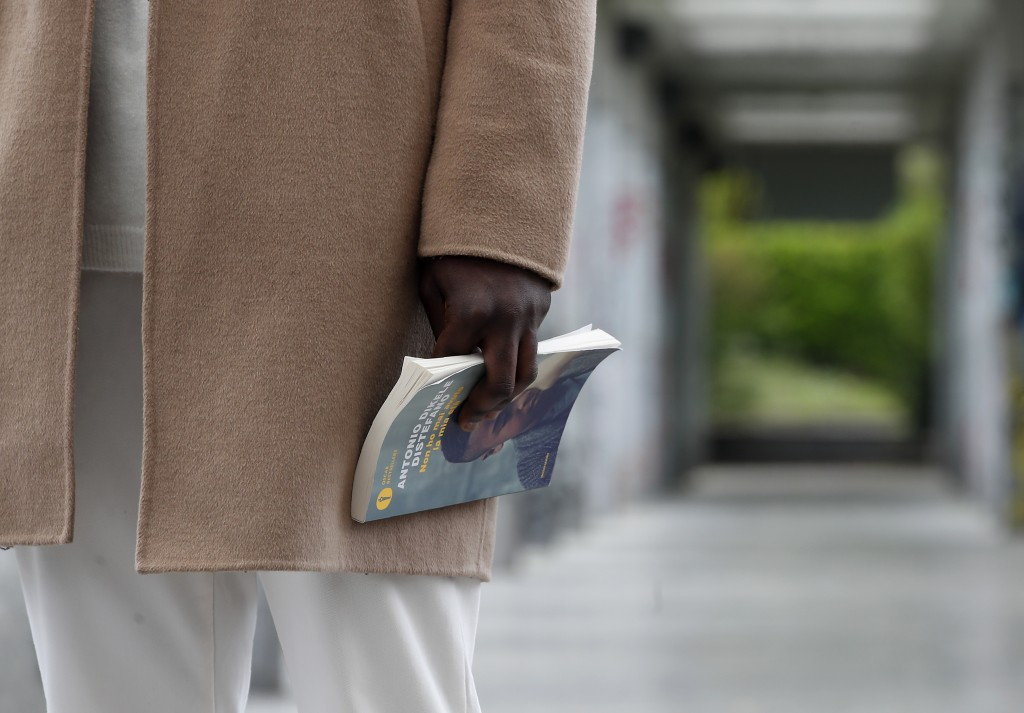 Author and screenwriter Antonio Dikele Distefano holds a book as he talks with the Associated Press in Milan, Italy, Tuesday, April 27, 2021. The Netf...