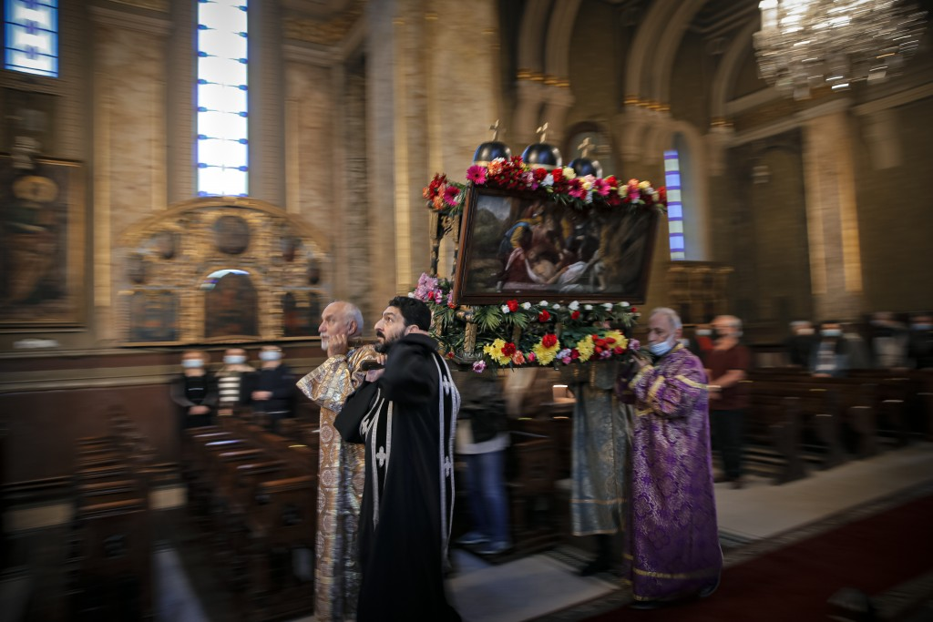Clergymen carry a structure symbolizing the tomb of Jesus Christ during a Good Friday religious service, at the Armenian Church in Bucharest, Romania,...