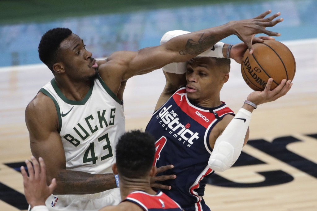 Washington Wizards' Russell Westbrook, right, looks to pass around Milwaukee Bucks' Thanasis Antetokounmpo (43) during the first half of an NBA basket...