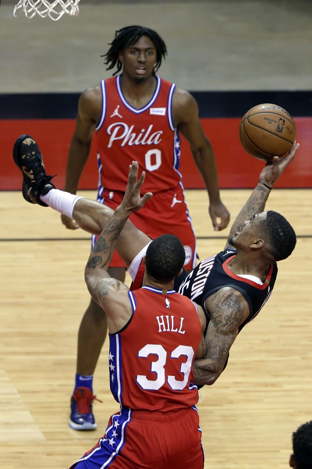 Houston Rockets forward DaQuan Jeffries, right, falls backward on his shot attempt between Philadelphia 76ers guard Tyrese Maxey (0) and guard George ...